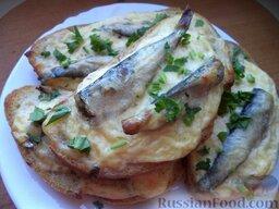 Горячие бутерброды со шпротами и сыром: Подавать тосты со шпротами и сыром на стол сразу, в горячем виде.  Приятного аппетита!