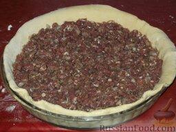 Фыдчин (осетинский пирог с мясом): Тесто положить на смазанную жиром сковороду, чтобы она покрывала ее края.     Затем уложить равномерно фарш по всей сковороде.