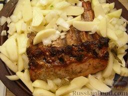 Свинина, запеченная с картофелем: Через час после начала запекания картофель с луком положить на противень рядом с мясом.  Чтобы края ребер не пережаривались, их можно прикрыть фольгой. Залить все горячей водой (1,5 стакана) и печь свинину с картофелем в духовке до готовности (30-40 минут).