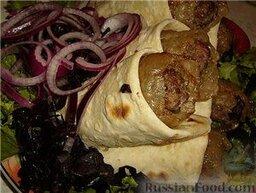 Люля-кебаб в лаваше (по алма-атински): Люля-кебабы уже готовы. Осталось только все собрать.  Вынуть противень из духовки. Каждую люляшку завернуть в лаваш, выкладывать люля-кебабы на блюдо с зеленым салатом, сверху - маринованный лучок, оформить помидорами и нарезанным крупно базиликом. Подавать люля-кебабы на стол сразу - есть только горячими.   Приятного аппетита!