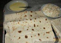 Хачапури из лаваша: Как приготовить хачапури из лаваша:    Кефир и яйца взбиваем вместе.  Сыр натираем на крупной терке, творог солим и смешиваем с сыром.   Противень смазываем маслом и выкладываем на него лаваш так, чтобы одна сторона была больше.