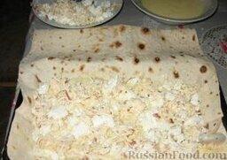 Хачапури из лаваша: Второй лаваш рвем на крупные куски. 1/3 часть их смачиваем в кефире с яйцом и выкладываем на сухой лаваш. Сверху равномерно распределяем половину сыра.