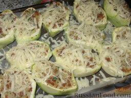 Патиссоны, фаршированные рисом и мясом: Через 40 минут достанем патиссоны и посыплем их тертым сыром. Отправим фаршированные патиссоны еще на 10 минут в духовку.
