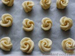 """Творожное печенье """"Розочки"""": Разогреть духовку до температуры  180 градусов. Выложить готовое творожное печенье на противень, покрытый бумагой для выпечки."""