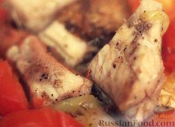 Морской окунь с овощами: Добавить куски рыбы. Накрыть крышкой и тушить рыбу с помидорами и луком до готовности.