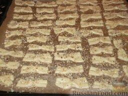 Печенье «Не пропадать же рассольчику»: Противень застелите пергаментом и смажьте маргарином или маслом. Перенесите на противень бантики.    Приготовленные бантики смажьте яйцом и посыпьте сверху измельченными грецкими орехами.
