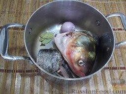 """Домашняя уха """"из топора"""": Кусочки рыбы, или в моем случае голову и хвост, помойте под проточной водой и положите в кастрюлю. Луковицу очистите и также положите в кастрюлю. Добавьте душистый перец горошком и лавровый лист. Налейте воду и поставьте на плиту вариться бульон."""