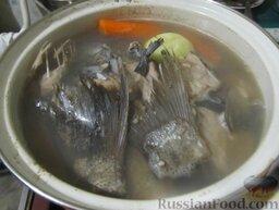 Уха наваристая с рисом: С вскипевшего бульона снять коричневую пену. Положить в кастрюлю лук и разрезанную морковь.   Варить бульон, не накрывая кастрюлю крышкой, около 20 минут. За это время большая часть жидкости должна выкипеть.