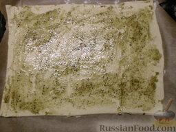 Пицца на скорую руку: Застилаем пергаментной бумагой противень.  Выкладываем на него лист слоеного теста. Прокалываем его, чтоб он не вздулся при выпекании.  Смазываем лист теста приготовленной смесью.