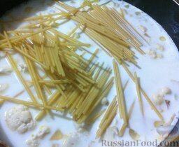 Спагетти, запеченные с тунцом: Выложите в сковороду спагетти, перемешайте и готовьте до полуготовности.