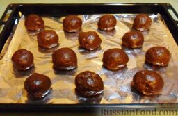 Кофейное печенье с кусочками шоколада: Чуть влажными руками скатать из теста шарики. Заготовки для печенья убрать на полчаса в морозильную камеру.  Затем выложить подмерзшие шарики на противень (можно на фольгу, но лучше – на пергамент).   Духовку разогреть до 180 градусов, потом поместить в неё противень с печеньем. Время выпечки кофейного печенья с кусочками шоколада зависит от размера