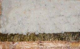 Урамаки-роллы с семгой и икрой мойвы: Равномерно выложить рис на лист нори.   Выложить необходимо со смещением вперед на 1 см, с противоположной стороны отступить 1 см и оставить полоску листа нори без риса. Эта полоска понадобится для того, чтобы заклеить ролл. Не забывайте смачивать руки каждый раз, когда берете новую порцию риса. Иначе рис будет прилипать к рукам.   Затем завернуть коврик и хорошо прижать.