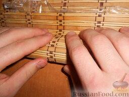 Урамаки-роллы с семгой и икрой мойвы: Свободную от риса полоску листа нори необходимо смочить водой.   Взять верхний край бамбукового коврика и плотно завернуть. Старайтесь придерживать начинку. Затем завернуть циновку с другой стороны или немного отодвинуть ролл от себя и опять завернуть, кому как проще.