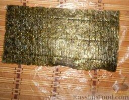 Урамаки-роллы с семгой и икрой мойвы: Застелить циновку пищевой плёнкой или полиэтиленовым пакетом.  Выложить лист нори на циновку глянцевой стороной вниз.  Если лист нори большой, то нужно разрезать его пополам.