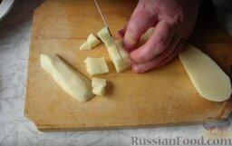 Рассольник с консервированным лососем: Нарезаем средним кубиком картофель и отправляем вариться в 2 л воды вместе с рисом.