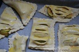 Слойки с яблоками и корицей: Готовые слойки выкладываем на лист, застеленный пергаментом. Взбиваем яйцо вилкой и смазываем слойки сверху.