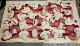 Пицца из слоеного теста, с курицей и грибами: Промыть грибы проточной холодной водой, снять верхнюю плёночку и разрезать на 4 части. Выложить шампиньоны следующим слоем.