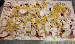 Пицца из слоеного теста, с курицей и грибами: Посыпьте кукурузой. Отправьте пиццу в разогретую духовку примерно на 20 минут (t=180°С). За 5 минут до конца посыпьте пиццу сыром, натертым на средней терке.