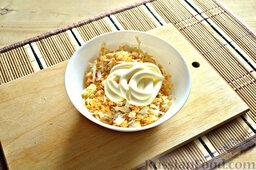 Роллы из блинчиков с крабовыми палочками: Подготовим начинку для роллов из блинчиков. Натрем отварные куриные яйца, добавим к ним пропущенный через пресс чеснок. Заправим яичную начинку майонезом. Перемешаем.