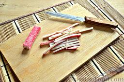 Роллы из блинчиков с крабовыми палочками: Крабовые палочки извлекаем из упаковки. При помощи ножика нарезаем на тонкие полоски.