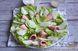 Салат с колбасой: На подготовленное блюдо или тарелку выкладываем сначала листья капусты. Затем выкладываем овощи: огурец и редьку, по вкусу солим. На тарелку красиво и аккуратно выкладываем колбасные трубочки.