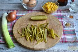 Салат с кукурузой и колбасой: Маринованные огурцы нарезаем тонкой соломкой.     В салатнице или на блюде смешиваем кукурузу, колбасу, перец, репчатый лук, лук-порей, огурцы и яйца.