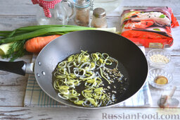Фунчоза с курицей и овощами: Обжариваем колечки лука-порея и чеснок на растительном масле 2 минуты.