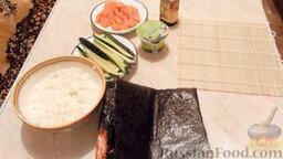 Роллы с огурцом и форелью: Подготовить ингредиенты для приготовления роллов с огурцом и форелью.   Также понадобится бамбуковая циновка, чтобы было удобнее заворачивать роллы.    Заранее отварить рис (на 0,5 стакана риса - 1 стакан воды).   Помыть огурец и нарезать длинными полосками.   Нарезать красную слабосоленую рыбу.