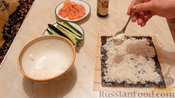 Роллы с огурцом и форелью: Далее выложить мягкий сыр поверх риса, распределяя его по центру.