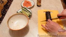 Роллы с огурцом и форелью: Переложить ролл на доску. Нарезать острым ножом на одинаковые кусочки.