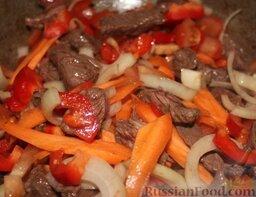 Лагман из говядины: Бросить к мясу сначала лук, морковь и болгарский перец, обжарить 3 минуты.