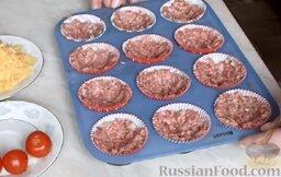 Мясные маффины с грибами: В силиконовые формы для кексов поместить бумажные формочки. В каждую форму аккуратно выложить по 2-3 ст. ложки мясного фарша и хорошо разровнять.