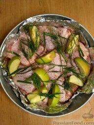 Курица, запеченная с яблоками: Вымойте яблоки, нарежьте дольками, добавьте в форму для выпекания. Зелень укропа распределите по курице. Мелко нарежьте чеснок и добавьте в форму. Также для аромата добавьте листья лаврушки.