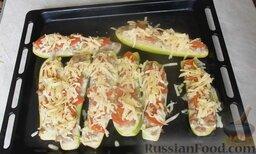 Молодые кабачки с фаршем, помидорами и сыром: Сыр натереть на крупной тёрке. Достать противень из духовки, посыпать кабачки тёртым сыром и отправить лодочки из кабачков с мясным фаршем в духовку еще на 5 минут.