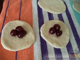 Жареные пирожки  с вишнями: Колобок из теста раскатать в кружок, толщиной как на вареники. На каждый кружок выложить вишню (3-5 шт.)