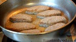 Котлеты рыбные (из карася): Разогреть растительное масло, выложить рыбные котлеты из карася в горячее масло, накрыть крышкой и жарить 2 минуты на среднем огне.