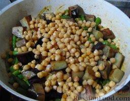 Овощное карри: Добавьте нут, соевый соус и лимонный сок, перемешайте. Залейте бульоном или водой, чтобы жидкость была на 2 см ниже уровня содержимого сковороды. Накройте крышкой и тушите овощное карри минут 7-10, до готовности стручковой фасоли. Посолите овощное карри по вкусу.