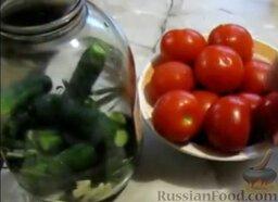 Малосольные помидоры и огурцы (горячий способ): Уложить в банку половину огурцов.