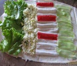 Рулет из лаваша с крабовыми палочками: Возьмите один лаваш, у одного края выложите салатные листья, дальше яйца, развернутые крабовые палочки и огурец.