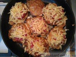Отбивные с сыром и помидорами: Как только отбивные будут готовы, сверху каждого куска мяса выкладывайте кольца помидора, присыпьте сыром, натертым на крупной терке. Дайте постоять отбивным под крышкой около 5 минут.