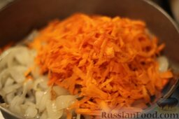 Аджапсандали (тушеные овощи): На отдельной сковороде обжариваем полукольца лука. Высыпаем в лук натертую на средней терке морковь. Это поможет нам сделать и лук, и морковь вкуснее.